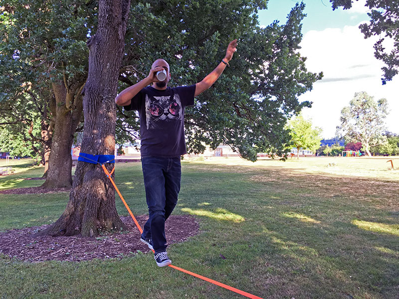 Alexis J. Villegas Drinking From a Cup While Slacklining at the Park